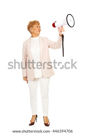 Senior smiling woman screaming through a megaphone