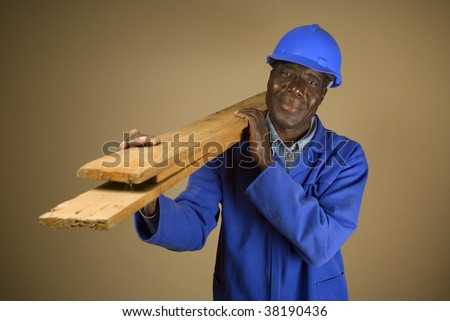 Senior South African or American plumber, carpenter or builder with wooden planks