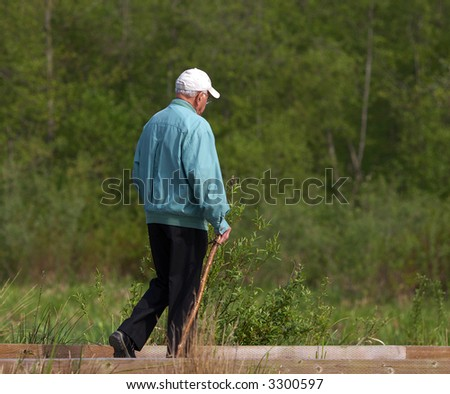 senior taking a walk in the park - stock photo