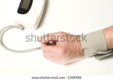 senior taking blood pressure over white - stock photo