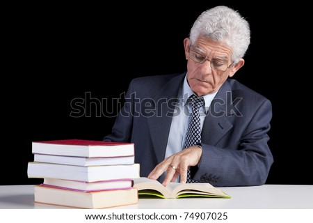 Senior teacher reading some books (isolated on black) - stock photo