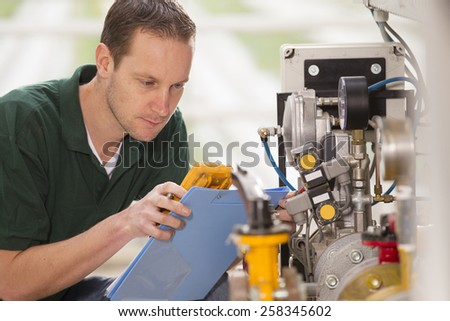Senior technician repairing agriculture machinery in a greenhouse - stock photo