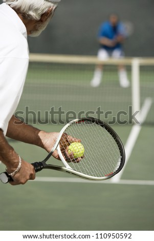 Senior tennis player with racket ready to serve a tennis ball - stock photo