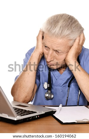 Senior thoughtful doctor sitting at table with notebook. Isolated white background
