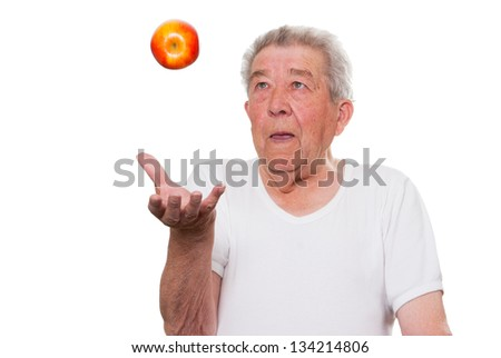Senior throws an apple into the air - stock photo