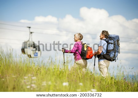 Senior tourist couple hiking under cableway