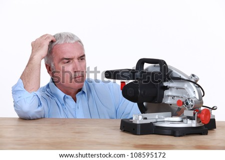 senior trying to understand how a machine works - stock photo
