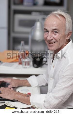 Senior typing on hip laptop - stock photo