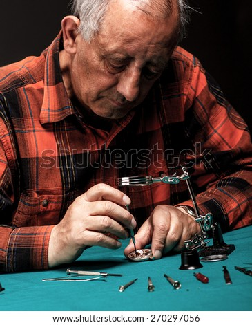 Senior watchmaker repairing an old pocket watch. Looking through a magnifying glass - stock photo