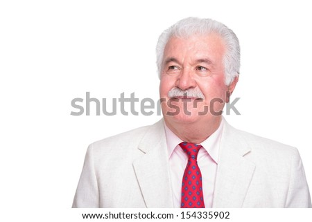 Senior white hair genlteman man with a red tie and beige suite looking his right upper side trustfully