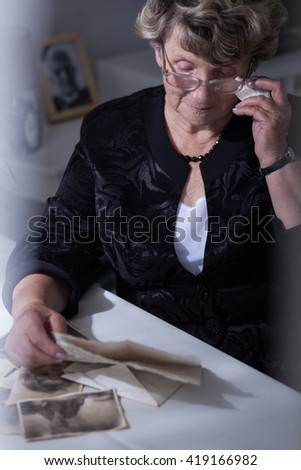 Senior widowed woman reading old letters from her husband - stock photo