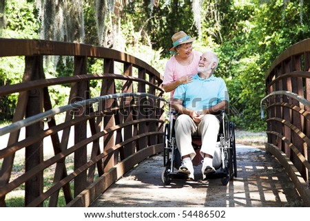 Senior wife takes her disabled husband on a walk through the park. - stock photo