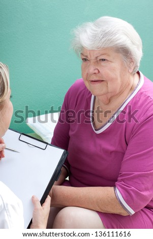 senior with blond doctor and clipboard - stock photo
