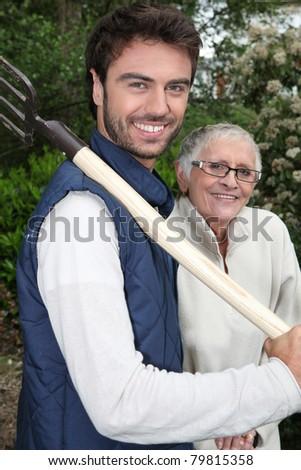 Senior with gardener and fork - stock photo