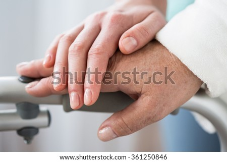 Senior with walking frame and helpful hand - stock photo