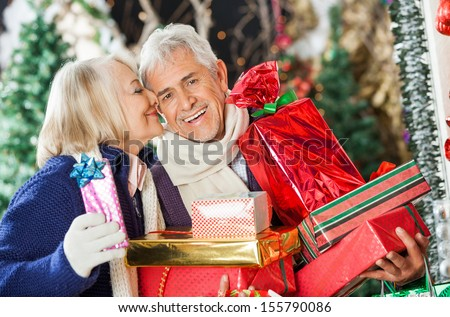 Senior woman about to kiss man holding Christmas presents at store - stock photo
