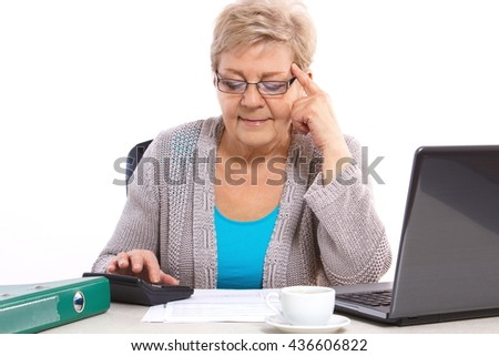 Senior woman, an elderly pensioner counting utility bills at her home, concept of financial security in old age