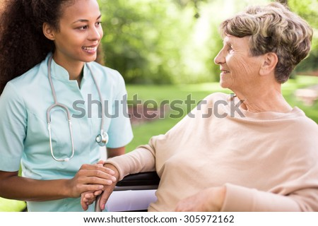 Senior woman and doctor spending time in the garden - stock photo
