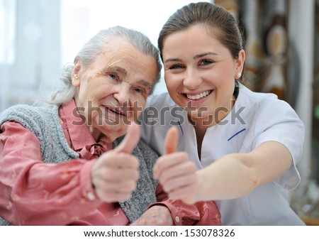 Senior woman and female nurse are showing thumbs up - stock photo