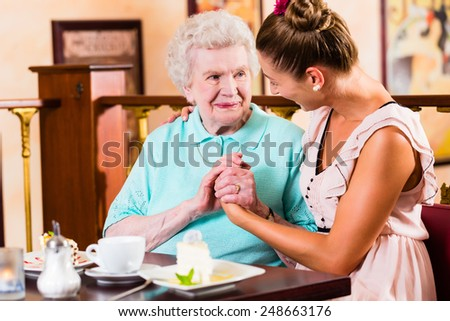 Senior woman and granddaughter drinking coffee and eating cake in cafe - stock photo