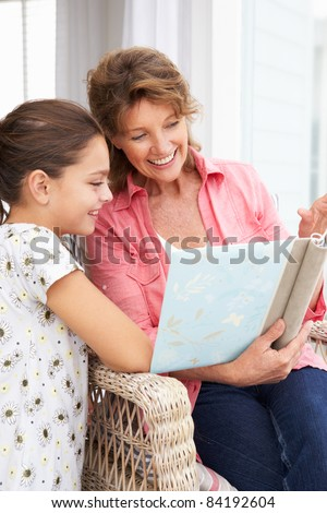 Senior woman and granddaughter with photo album - stock photo