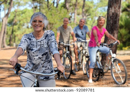 Senior woman and her friends riding bikes through the countryside - stock photo