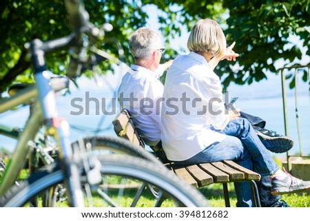 Senior woman and man at rest on bike trip sitting on a bench