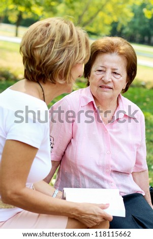 Senior woman and mature daughter sitting on the park bench. - stock photo