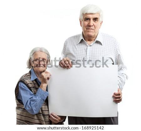 Senior woman and mature man holding a blank billboard - stock photo