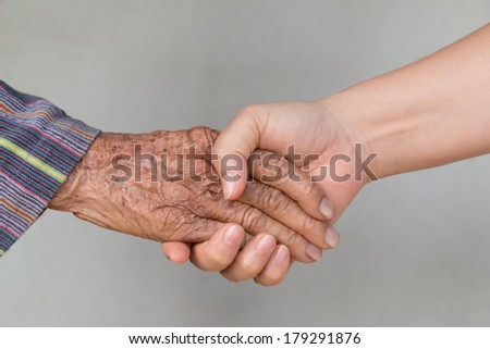 Senior woman and young woman holding hands  - stock photo