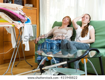 Senior woman and young woman sits on the sofa resting at home