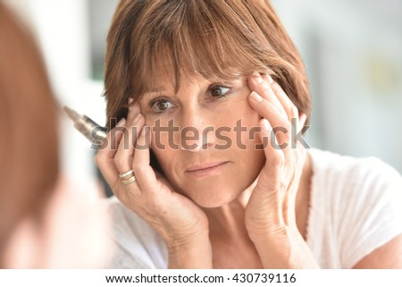 Senior woman applying eye concealer - stock photo