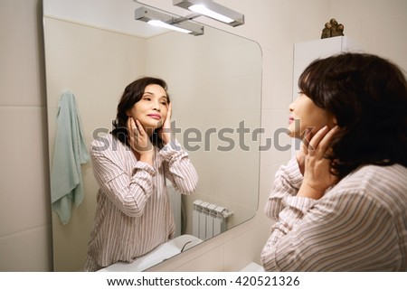 Senior woman applying lotion or anti-aging cream on her face standing in front of the mirror in the modern bathroom. Female mature Asian female examiming her reflection for wrinkles or ageing signs  - stock photo
