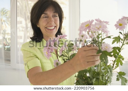 Senior woman arranging flowers in vase - stock photo