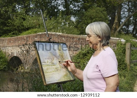 Senior woman artist painting by a river and bridge. - stock photo