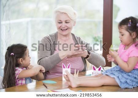 Senior woman assisting granddaughters in art work at home - stock photo