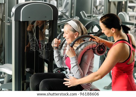 Senior woman at gym exercise with personal trainer on machine - stock photo