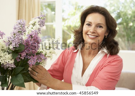 Senior Woman At Home Arranging Flowers - stock photo