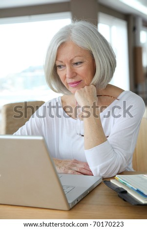 Senior woman at home in front of laptop computer - stock photo