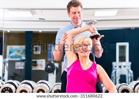 Senior woman at sport exercise with dumbbell in gym with trainer to gain strength and fitness