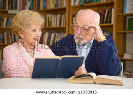Senior woman at the library, showing her husband a passage in a book. - stock photo