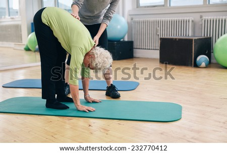 Senior woman bending forward and touching her toes being helped by gym instructor. Elder woman doing back exercise with help from physical therapist at gym. - stock photo