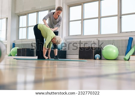 Senior woman bending forward and touching her toes being helped by personal trainer at health club. Elder woman doing back exercise with help from physical therapist at gym.
