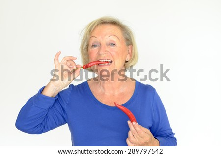 Senior woman biting a fresh red hot chili pepper while looking at the camera with a smile, upper body over a grey background