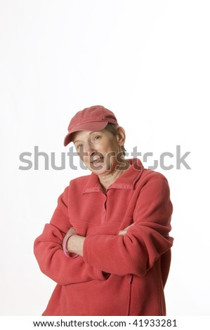 Senior woman breast cancer survivor in pink cap with arms folded set against a white background.