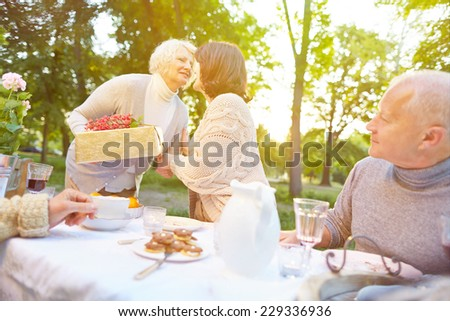 Senior woman bringing gift to birthday party in a summer garden - stock photo