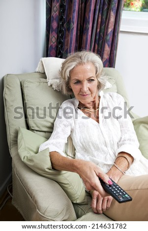 Senior woman changing channels with remote control on armchair at home - stock photo
