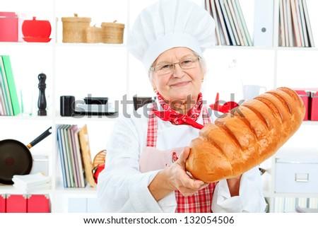 Senior woman chef cooks in the kitchen. - stock photo