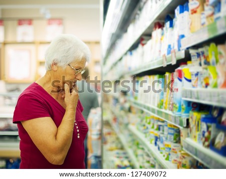 Senior woman choosing a dairy products at supermarket - stock photo