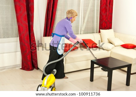 Senior woman cleaning home with vacuum cleaner - stock photo